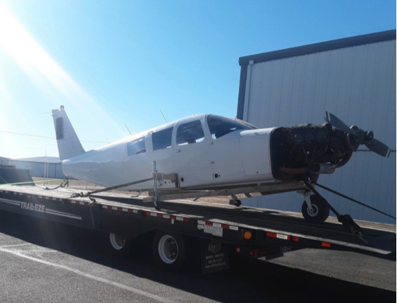 Flatbed towing airplane
